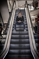Going up (Dannis van der Heiden) Tags: modelphotography model wouter escalator atmosphere cool hudsonbay shoes amersfoort warehouse clothing man sitting goingup netherlands nikond750 d750 nikkor50mmf18g male streetphotography people ceiling fashion symmetry lights persona jeans dude original shop