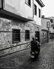 commuting (zeNat Photography) Tags: blackandwhite blackwhite bnw monochrome streetphotography street urban urbanlife couple motorcycle bike scooter house streetlife