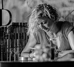Candid ( On The Phone) Sunset Cafe-Bar (Myrina Town- Limnos - Greece) (Monochrome)  (Olympus OM-D EM1-II & M.Zuiko 40-150mm f2.8 Pro Telephoto Zoom) (markdbaynham) Tags: greece greek grecia greka limnos lemnos em1 hellas hellenic myrina mypina myrinatown olympus omd olympusomd olympusgreece olympusmft olympusem1 em1mk2 em1ii em1mark2 csc evil m43 micro43 microfourthird microfourthirds mft mzd mz zd mzuiko zuikolic 40150mm olympusprolens prozoom telephoto m43rd travel micro43rd town northaegean northaegeanisland aegeanisland people bw monochrome blackwhite sunsetcafe