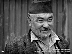 2018-05a Nepal (03bw) (Matt Hahnewald) Tags: matthahnewaldphotography facingtheworld people character head face eyes expression lookingcamera beard unshaved moustache stubble pencilbehindear headwear cap necklace dhakatopi hat consent concept humanity living work dedication commitment nature travel culture optimism local rural carpenter manegeira helambu nepal asia asian sherpa hyolmo nepali individual oneperson male adult elderly man photo physiognomy nikond3100 primelens nikkorafs50mmf18g 50mm 4x3 horizontal street portrait closeup headshot threequarterview outdoor village workshop mono blackandwhite monochrome greyscale vignette posing overweight clarity respect
