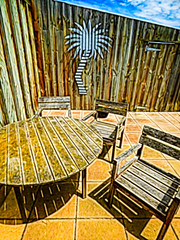 A Sunny Day (Steve Taylor (Photography)) Tags: digitalart door fence tableandchairs brown bright blue yellow tile wooden newzealand nz southisland canterbury christchurch tree corrugated perspective hinge palmtree shadow corrugatediron sunny sunshine