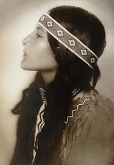 """Little Bird: """"Proud Heritage, Piegan."""" Photograph by Roland Reed, 1915.  Postcard 153 published by Azusa Publishing, Inc. (1991) (lhboudreau) Tags: nativeamericans nativeamerican americanindian americanindians portrait vintagephoto vintagephotograph sepia sepiatoned print vintagephotography rolandreed proudheritage piegan proudheritagepiegan 1915 postcard postcards vintagepostcard vintagepostcards azusa azusapublshing azusapublishinginc 1991 postcard153 headband blackhair indiansquaw squaw proud profile monochrome blackandwhite blackwhite rolandwreed pictorialist focus lighting littlebird"""