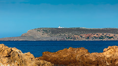 Lighthouse in the distance (Nicola Pezzoli) Tags: menorca baleares baleari island nature spain sea minorca isola cala pregonda far de cavalleria lighthouse red rock zoom
