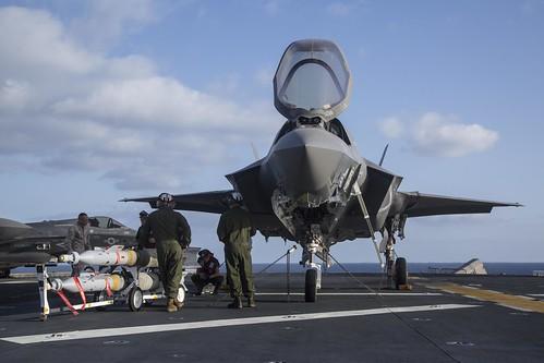 Marines guide ordnance toward an F-35B Lightning II.