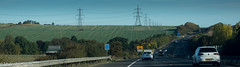 Power Across The Landscape 3 (M C Smith) Tags: pylons motorway m11 pentax k3 fields rolling hills lines green grass sky blue pylon lights cars car van white powerlines road hill yellow sign signs barriers trees hedges bushes clouds shadows