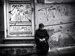 Lines (Feldore) Tags: tallinn street photography elderly lady woman sitting lined face contemplation estonia hat thoughtful feldore mchugh em1 olympus 1240mm graffiti
