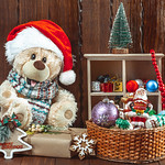 Christmas background with a teddy bear, Christmas toys and gifts on a wooden table. The concept of a children's holiday, family celebration thumbnail