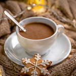 Hot coffee with gingerbread on the background of a knitted scarf and Christmas garland thumbnail