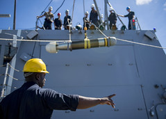 Sailor supervises the lowering of a Mark 46 torpedo