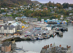 Oban Station and Harbour (Rollingstone1) Tags: oban scotland boats view scenery landscape hillside hill buildings art artwork water boat sea ferryterminal harbour station train ferry fishingboat autumn trees roof chimney spire track line road vehicles cars bus windows
