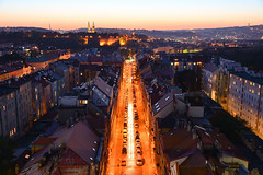 Another evening view over Praha 2 district: 25 minutes after sunset (Pavel's Snapshots) Tags: dramatic quiet street road way direction path orange dusk evening late sky houses prague praha czech czechrepublic europe urban distant valley density european nikon d750 35mm district area old historic historical roof tileroof traditional residential haze church straight bright lights vivid symmetry rectange block wall magenta landscape hills dark