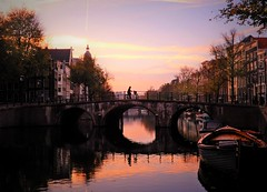 Sunrise in Amsterdam (Clare-White) Tags: canal amsterdam bridge sunrise water reflection early dutch cyclist bike buildings boats trees light colour outside nikon arches 3 matchpointwinner mpt670