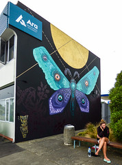 A Moth's Perspective (Steve Taylor (Photography)) Tags: moth moon antennae cinzah street prints otautahi 2017 flipflops jandals bottle bin dustbin mobile talking ara butterfly shorts barelegs phone insect building blue black mauve purple yellow lady woman newzealand nz southisland canterbury christchurch newbrighton bush perspective