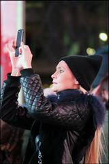 Shooting without Looking - Times Square, NYC (TravelsWithDan) Tags: woman blond candid night photographer womantakingacellphonephoto blackcoat blackhat longblondhair winter nyc newyork timessquare canong3x theotherphotographer streetportrait