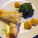 Fisch im Teigmantel mit Spinat und Duchess Kartoffeln auf weißem Teller