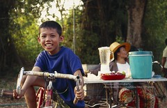 near Nong Khai, young boy at a Thai party (blauepics) Tags: thailand east city stadt nong khai thai face gesicht portrait mensch human kids children kinder people menschen leute party fest bycicle fahrrad bike smile lachen