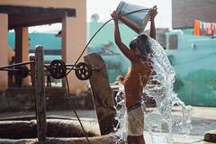 Boy Dumping Well Water, Bath (AdamCohn) Tags: adam cohn uttar pradesh india mathura vrindavan bathing boy bucket holi splash water well wwwadamcohncom adamcohn uttarpradesh govardhan flickrtravelaward