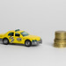 Taxi and stack of coins isolated on white