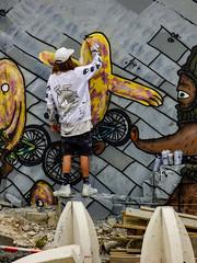 Painting on the Dside (Steve Taylor (Photography)) Tags: dside bmd art graffiti mural streetart bollard brown black yellow aerosol spray concrete wood man newzealand nz southisland canterbury christchurch city cap sweatshirt shorts bike alien budgie bicycle cycle