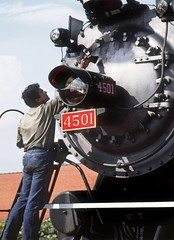 Southern Railway steam locomotive # 4501 smoke box front is being cleaned for the next days Railfan Excursion Train assignment at Salisbury, North Carolina, August 1985 (alcomike43) Tags: southernrailway salisburynorthcarolina railfanexcursiontrain railroads trains cleaning maintenance employee steamteam crewman smokebox boilerfront headlight engine locomotive steamengine steamlocomotive baldwin 282 makido steam coal smoke 4501 photo photograph slide color old historic vintage classic