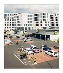 At the Lot (Thomas Listl) Tags: thomaslistl color urban parkinglot cars architecture würzburg 35mm mundane cityscape houses windows store supermarket topography