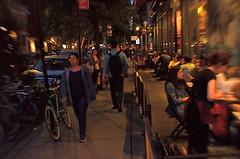 The Village (MPnormaleye) Tags: crowds nyc manhattan utata urban neighborhoods diners restaurant neon streetlamps brownstone sidewalk tables chair bicycle lensbaby 35mm seeinanewway