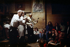 50-709 (ndpa / s. lundeen, archivist) Tags: nick dewolf nickdewolf color photographbynickdewolf 1973 1970s film 35mm 50 reel50 neworleans louisiana nola frenchquarter livemusic jazz jazzband preservationhall band group musician musicians billieanddedepierce jazzmusic jazzmusicians preservationhalljazzband dedepierce billiepierce piano people audience sittingonthefloor seated sitting paintingsonthewall interior stage trumpet trumpeter trumpetplayer player whiteshirt tie blacktie grayhair whitehair oldman players clarinet banjo ties jazzclub club show performance