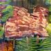 Spieße mit Schweinefleisch in einer Vitrine mit Salat und grünen Chilis