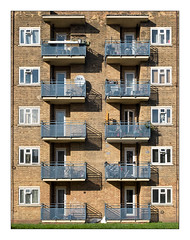 Council Flats, Hackney, East London, England. (Joseph O'Malley64) Tags: thebuiltenvironment newtopography newtopographics building structure britishdocumentaryphotography documentaryphotography architecture architecturalphotography housing homes dwellings abodes highrise highrisehousing towerblock urbanarchitecture eastlondon eastend london england uk britain british greatbritain steelreinforcedconcretestructure windows upvcdoubleglazing balconies steelrailings steelmesh brickwork bricksmortar cement pointing brickinfills wiring cables cabletv fibreopticcables curtains personalpossessions satellitedish doors balconydoors grass bikes chairs washingline urban urbanlandscape flats multistoreybuilding housingassociations councilowned privateownership fujix fujix100t accuracyprecision