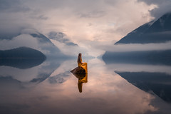 Stranded in a Dream (Elizabeth Gadd) Tags: lake water still reflection mirror clouds mountains fog foggy misty mist girl woman dress yellow gold sunrise nature landscape portrait magical calm rock sitting