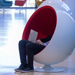 Mann bedient Laptop sitzend in einem Designer- Sessel thumbnail