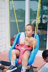 Swingin' with some Watermelon Juice (cloudsinmycoffeephotography) Tags: swing bright boy child childhood