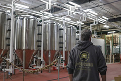 Taylor Lamm, owner of Oconee Brewing Company, walks by the distilleries, which manufacture the beer.