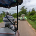Overloaded Motorbike driving in front of a TukTuk in Siem Reap
