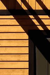 Shadows (Karen_Chappell) Tags: yellow brown black shadow abstract architecture quidividi newfoundland nfld canada rural lines paint painted clapboard wood wooden geometry geometric building diagonal atlanticcanada avalonpeninsula