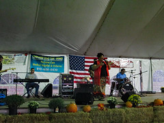 Gospel Music From Carla & Redemption. (dccradio) Tags: lumberton nc northcarolina robesoncounty tent entertainmenttent carlaandredemption carlaredemption gospelmusic gospelnight southerngospel stage instruments musicians sing singing singers flower floral flowers mum mums flag americanflag usa usflag unitedstatesflag oldglory drums drummer speakers keyboard keys hay straw bales pumpkins fall autumn canon powershot a3400is robesonregionalagriculturalfair fair countyfair robesoncountyfair fun entertainment communityevent