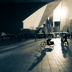 Reflecting sun shadows (Michiel Pols) Tags: building water architecture cityscape city scape street streets photo photography urban people person rotterdam netherlands nederland holland panasonic lumix gx9 vario 1260 f3556 3556 mft bike bikes bicycle road monochrome sky train station square