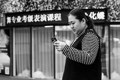 Her (Go-tea 郭天) Tags: qingdao shandong woman lady young fat portrait alone lonely phone cell cellular mobile network connexion data connected disconected virtual virtuality addiction drug technology reality canon eos 100d 50mm prime street urban city outside outdoor people candid bw bnw black white blackwhite blackandwhite monochrome naturallight natural light asia asian china chinese