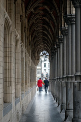 Underneath the arches. (James- Burke) Tags: visitors street people streetphotography corridors red man walking mechalan travel belgium couple fuji strolling woman columns tourism companionship candid