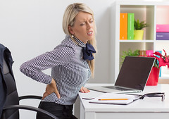 Woman having back pain while sitting at desk in office (duongdomo) Tags: backpain back pain ache woman painful problem health issue bad unhealthy muscle muscular sitting office desk working computer young suffer sprain spine stiff suffering unhappy people chair problems hurt latvia