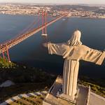 Luftaufnahme von hinten Cristo Rei Statue und Ponte 25 de Abril Brücke in Almada Lissabon thumbnail