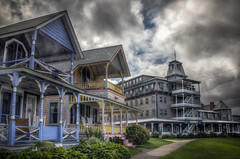 Two Houses and the Summercamp Hotel (donnieking1811) Tags: massachusetts oakbluffs marthasvineyard summercamphotel hotel houses buildings architecture porches stairs chairs sidewalk columns posts exteriors outdoors grass sky clouds hdr canon 60d lightroom photomatixpro