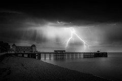 Night At The Pier by Simon Hadleigh-Sparks (Simon Hadleigh-Sparks) Tags: lightning pier sea night dark beach sky cloud bw blackandwhite building contrast horizon skyline light landscape monochrome nature outdoor simonandhiscamera vignette water weather waterfront