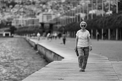 the road after perdition (dim.pagiantzas | photography) Tags: people woman street road port environment city town sea water construction face perdition bokeh grayscale monochrome blackandwhite trees walking walk perspective canon outdoor