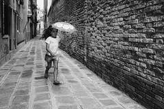 Girl Power (markfly1) Tags: italy italia venice europe girl power child children kids running sunshine umbrella shade speckled light bricks path pavement candid image street narrow passage textures bw black white mono monochromatic shadow bright nikon d750 35mm manual focus lens