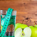 Green apples and a glass of water with measuring tape on wooden background. Diet concept