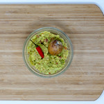High angle shot - Guacamole Avocado Dip - with red chili pepper and avocado kernel in glas bowl thumbnail