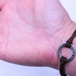 Leather Bracelet with metal trinket and the writing