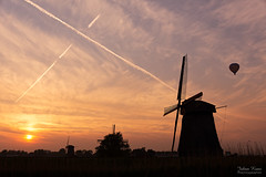 Gone with the Wind (Johan Konz) Tags: sunset orange sky stripes clouds windmill balloon landscape silhouette schermer polder schermerhorn netherlands lines nikon d7500 tree undermillc undermilld museummill uppermille