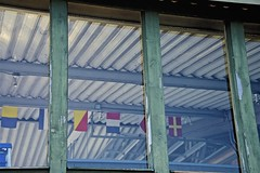 Afternoon At The Yacht Club (sswj) Tags: yachtclub window flags reflection bainbridgeisland washingtonstate composition availablelight existinglight naturallight nikon d600 nikkor28300mm abstractreality scottjohnson